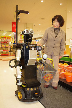Robovie-II Helping an Elderly Woman With Her Grocery Shopping.